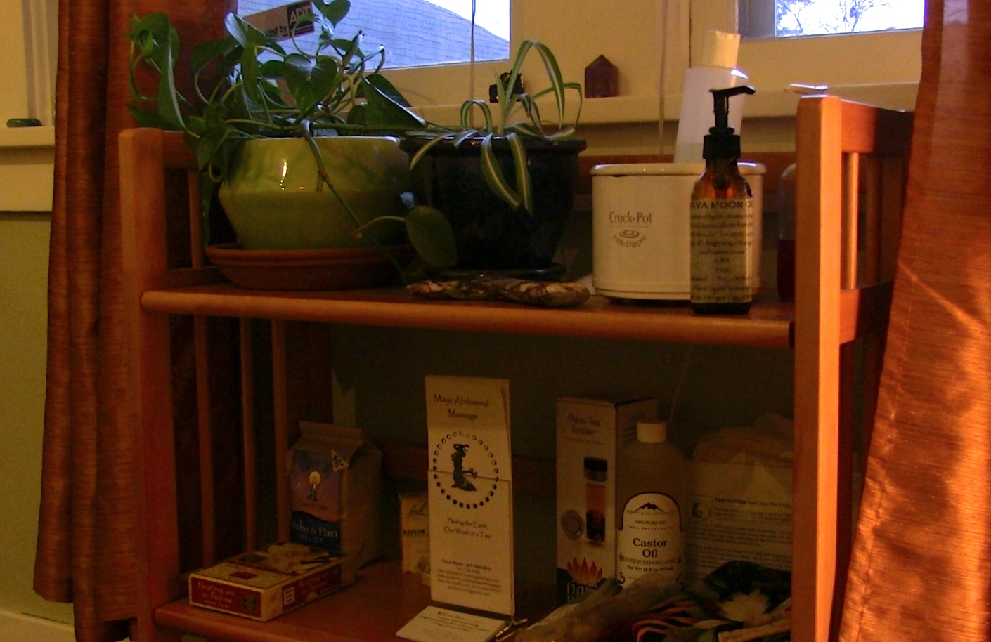 A shelf of plants and products, at Plant~Spirit~Massage